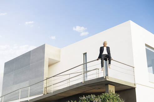 Businessman sitting on handrail in front of his modern house - SBOF02071