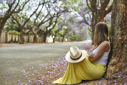 Woman leaning on a tree at a street with jacaranda trees in bloom, Pretoria, South Africa - VEGF00798