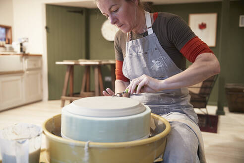 Woman working with a pottery wheel in her workshop - PMF00913
