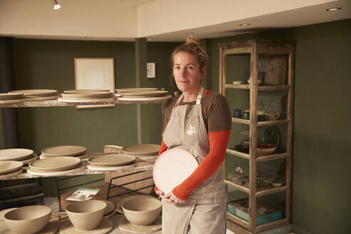 Female potter in her workshop at a shelf - PMF00916