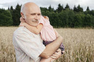 Portrait of senior man in an oat field carrying granddaughter on his arms - EYAF00689