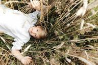 Portrait of blond boy with oat ear in mouth lying in an oat field - EYAF00692