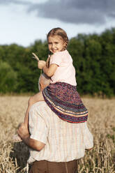 Portrait of happy little girl on grandfather's shoulders in an oat field - EYAF00701