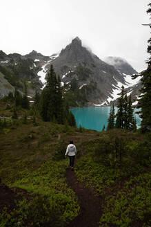 Tourist exploring wilderness, Alpine Blue Lake, Washington, USA - ISF22705