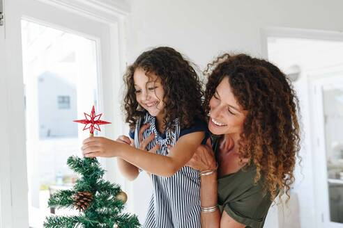 Mother helping daughter place star on Christmas tree at home - ISF22729