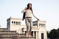 Portrait of young woman standing barefoot on stairs at Koenigsplatz, Munich, Germany - WFF00171
