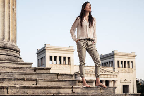 Barefoot young woman standing on stairs at Koenigsplatz relaxing, Munich, Germany - WFF00177