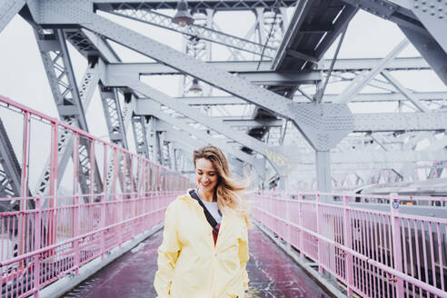 A woman wearing yellow raincoat, walking on a bridge and looking down, New York, USA - DAMF00220