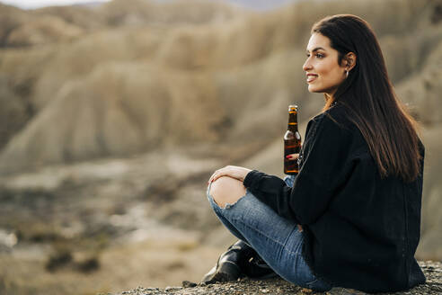 Young woman sitting in desert landscape drinking a beer, Almeria, Andalusia, Spain - MPPF00268