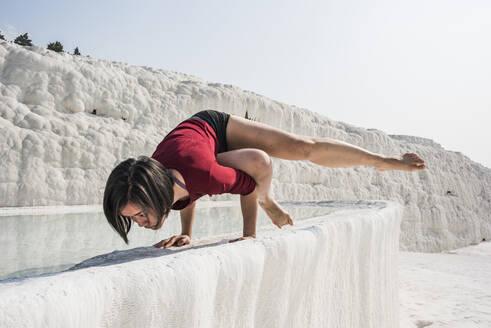 Woman practising yoga in cotton castle, Pamukkale, Denizli, Turkey - CUF53490