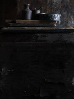 Rustic low key still life with ceramic bowl, jar and pot on cutting boards, surface level view - ISF22817