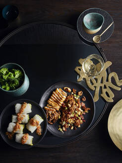 Rustic low key still life with dish of fungus cabbage roll and grilled whole squid on table, overhead view - ISF22898