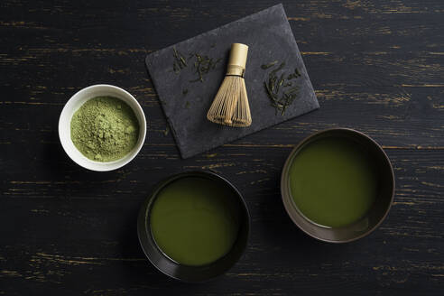 Still life of matcha tea preparation with whisk and bowls of matcha tea and tea powder, overhead view, low key - ISF22937