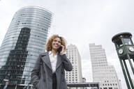 Smiling woman on the phone with office buildings in background, Berlin, Germany - AHSF01263