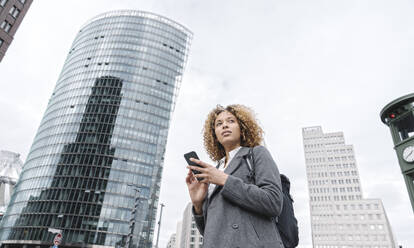 Woman holding smartphone with office buildings in background, Berlin, Germany - AHSF01266