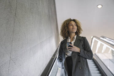 Woman holding cell phone on escalator - AHSF01269