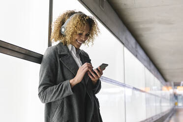 Smiling woman with headphones and smartphone - AHSF01272