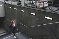 Woman walking up dtairs at a subway station, Berlin, Germany - AHSF01287