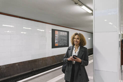Smiling woman with cell phone waiting in subway station - AHSF01293