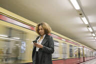 Woman using cell phone in subway station as the train comes in - AHSF01296