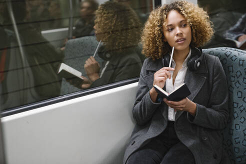 Woman taking notes on a subway - AHSF01299