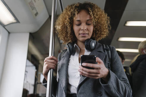 Woman using smartphone on a subway - AHSF01308