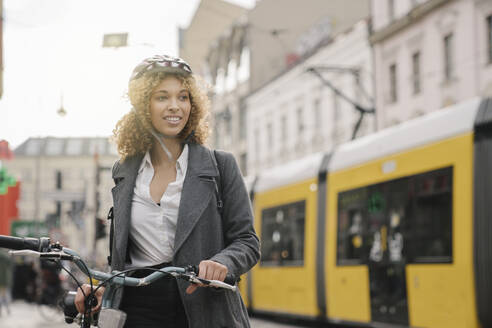 Woman with bicycle in the city, Berlin, Germany - AHSF01311