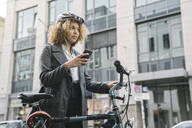 Woman with bicycle and smartphone in the city, Berlin, Germany - AHSF01317