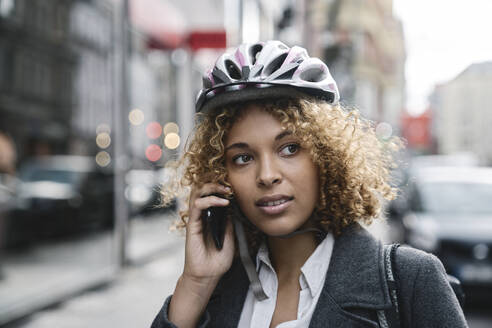 Portrait of woman with bicycle helmet talking on the phone in the city, Berlin, Germany - AHSF01320