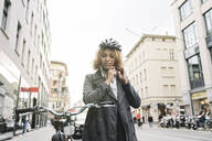 Woman putting on bicycle helmet in the city, Berlin, Germany - AHSF01323