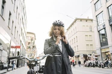 Woman putting on bicycle helmet in the city, Berlin, Germany - AHSF01323