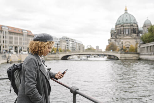 Tourist woman using smartphone in the city with Berlin Cathedral in background, Berlin, Germany - AHSF01326
