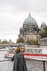 Happy tourist woman in the city at Spree river, Berlin, Germany - AHSF01329