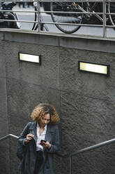 Woman using smartphone at the entrance of a subway station, Berlin, Germany - AHSF01341