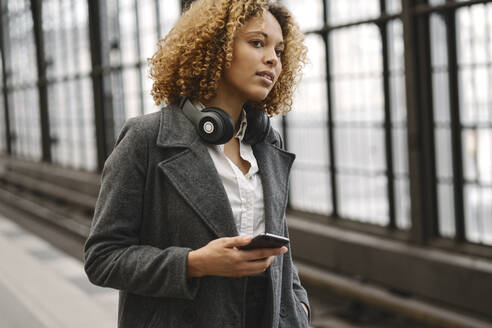 Woman with cell phone waiting in subway station - AHSF01344