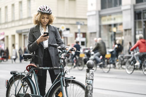 Woman with bicycle and smartphone in the city, Berlin, Germany - AHSF01347