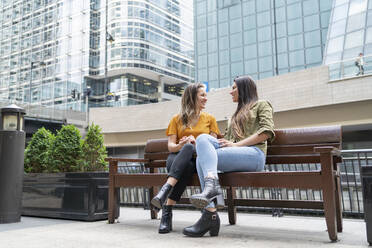 Happy lesbian couple sitting on a bench in the city, London, UK - FBAF00970