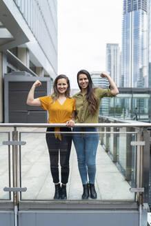Portrait of happy lesbian couple flexing muscles in the city, London, UK - FBAF00976