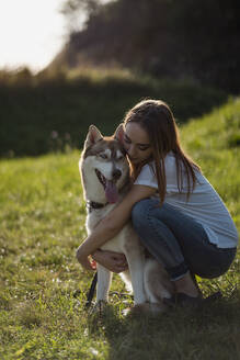 Young woman hugging her dog on a meadow - MAUF03082