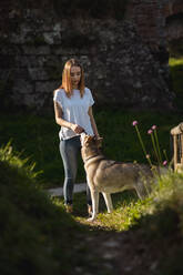 Yound woman with her dog outdoors - MAUF03088
