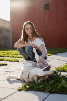 Portrait of young woman stroking her dog outdoors in the evening - MAUF03100