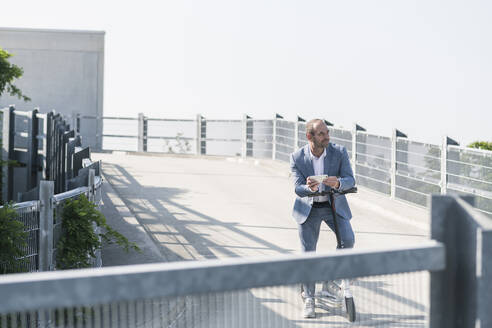 Mature businessman with e-scooter and smartphone on parking deck - UUF19699