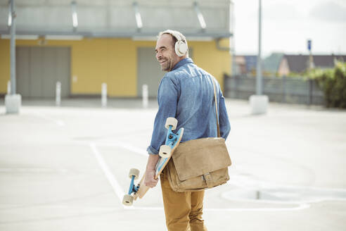 Happy casual mature man with headphones and skateboard walking on parking deck - UUF19711