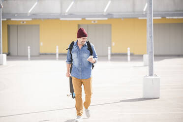Casual mature man with smartphone and skateboard walking on parking deck - UUF19714