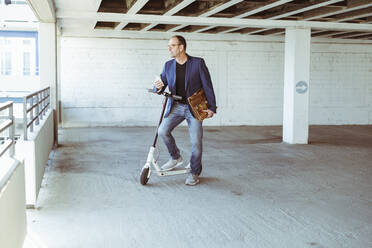 Mature businessman with e-scooter and smartphone in parking garage - UUF19717