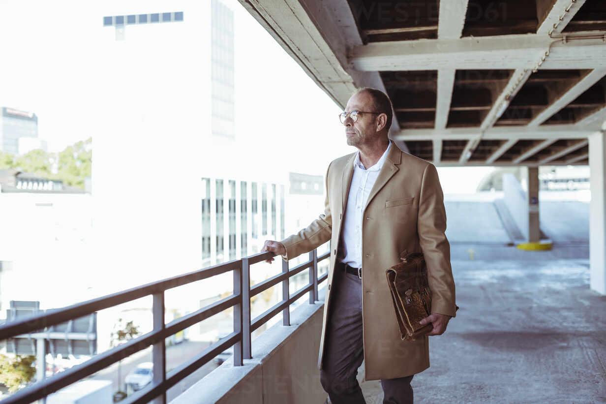 Mature businessman with briefcase standing on parking deck - UUF19720 - Uwe Umstätter/Westend61