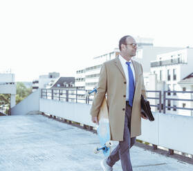 Mature businessman with skateboard and briefcase walking on parking deck - UUF19723