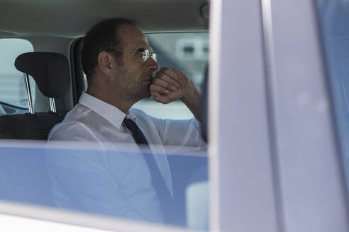 Portrait of thoughtful mature businessman in car - UUF19726