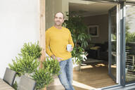 Mature man standing at terrace door at home with coffee cup - UUF19732