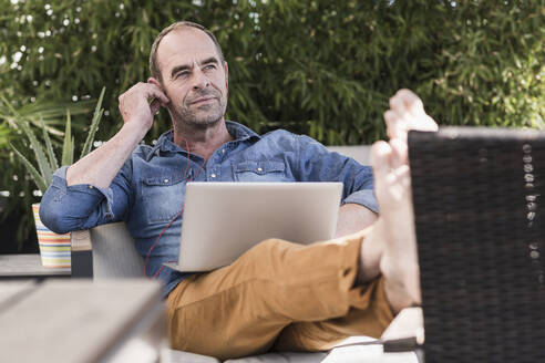 Mature man sitting on terrace with earphones and laptop - UUF19735